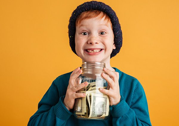 Young boy with huge smile holding jar of money